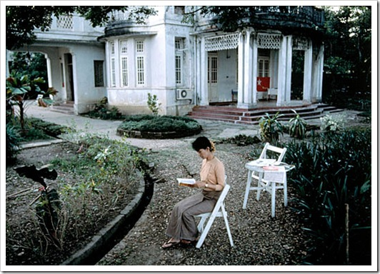 MYANMAR. Rangoon. 1995. Daw Aung San SUU KYI, nonviolent activist and winner of the 1991 Nobel Peace Prize, reads in her yard where she was under house arrest for 6 years.