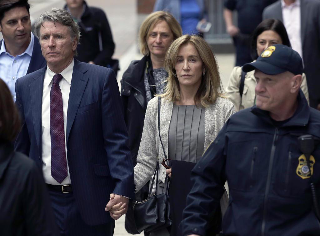 Va a declarar. Felicity Huffman, centro, sale de una corte federal con su hermano Moore Huffman Jr. (AP)