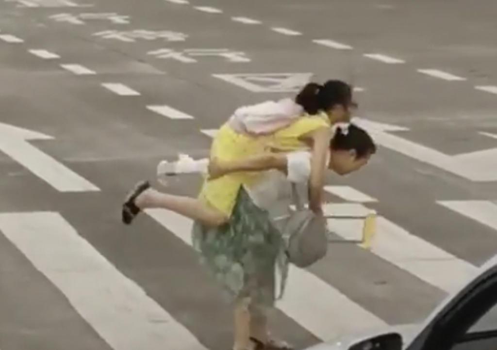 Carga a niña en muletas para ayudarla a cruzar la calle. Noticias en tiempo real