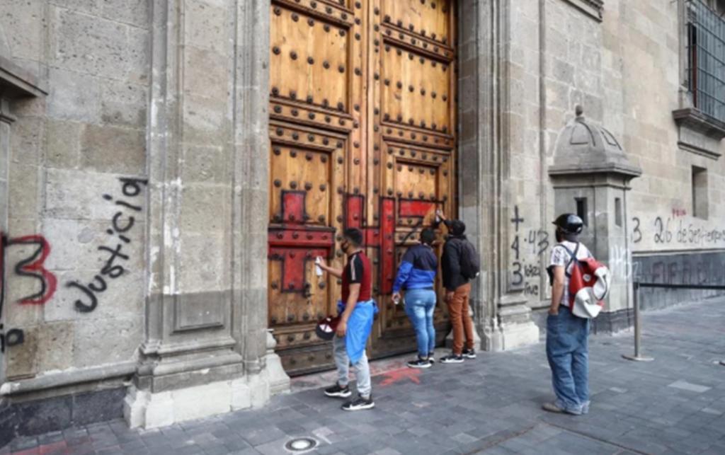 Hacen pintas en Palacio Nacional tras concluir la marcha por Ayotzinapa. Noticias en tiempo real